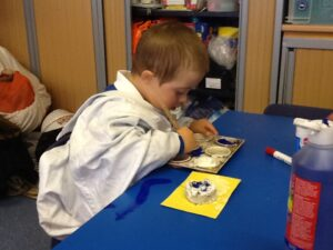 Down syndrome child painting at school