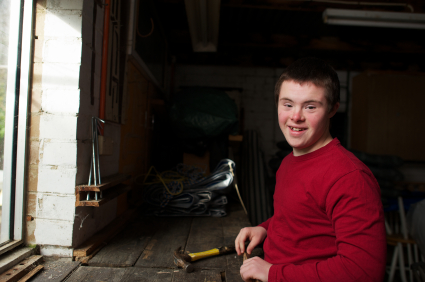 Teenager with Down syndrome working on his project in a garage.